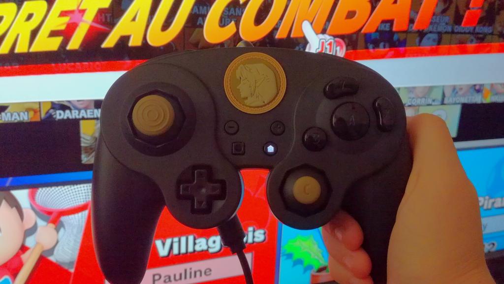 Photo du Wired Fight Pad Pro tenue en main sur fond d'écran de sélection des personnages de Super Smash Bros Ultimate